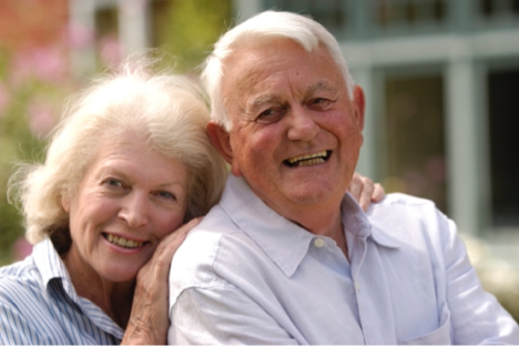 An aging couple smiling at the camera.