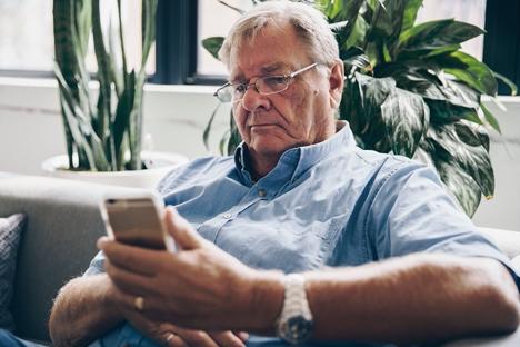 An elderly man using a smartphone.