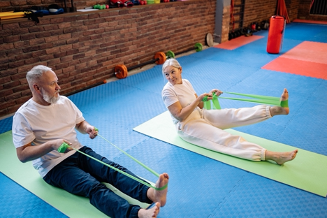 Two seniors staying active and healthy by exercising with resistance bands.