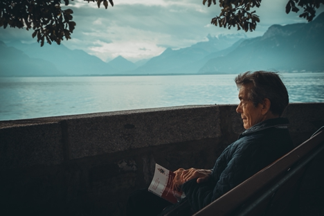 Elderly man sitting alone with a book looking at a water scenery.
