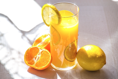 A glass of orange juice surrounded by oranges and lemons.